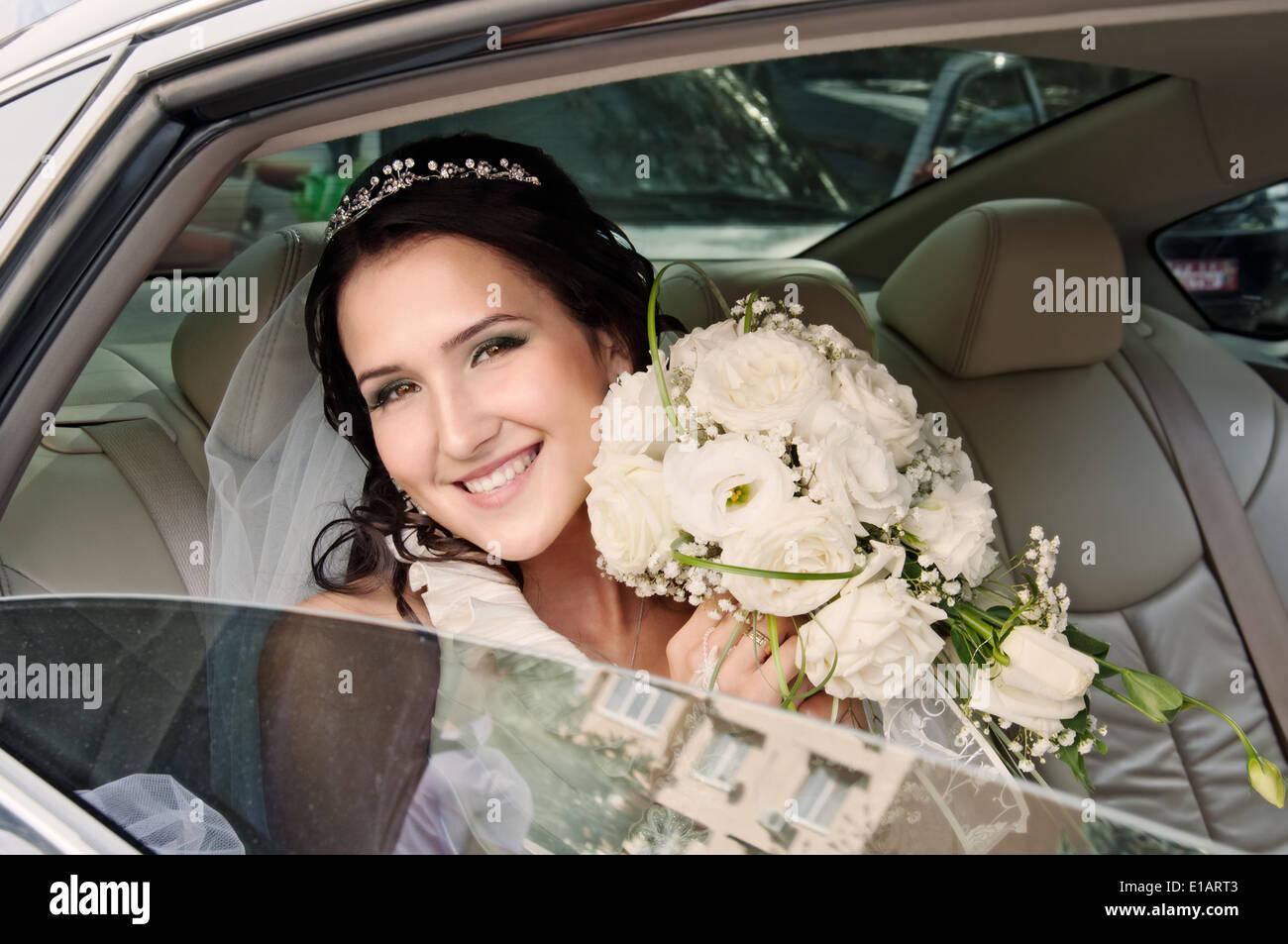 Feliz novia mirando afuera de la ventanilla. Día de la boda Imagen De Stock