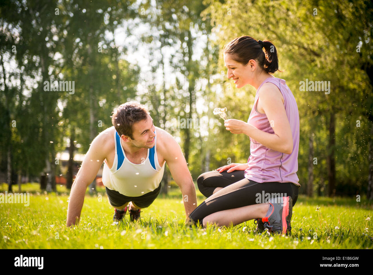 Hombre haciendo push-ups mientras la mujer está soplando sobre él - Semillas de diente de león en la naturaleza al aire libre Imagen De Stock