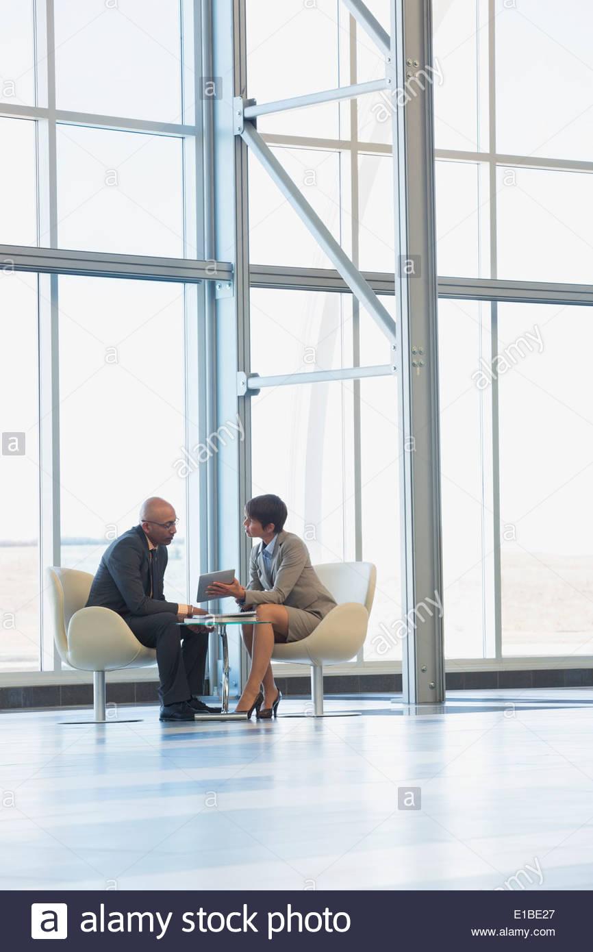Los hombres de negocios en el vestíbulo moderno y tableta digital Imagen De Stock