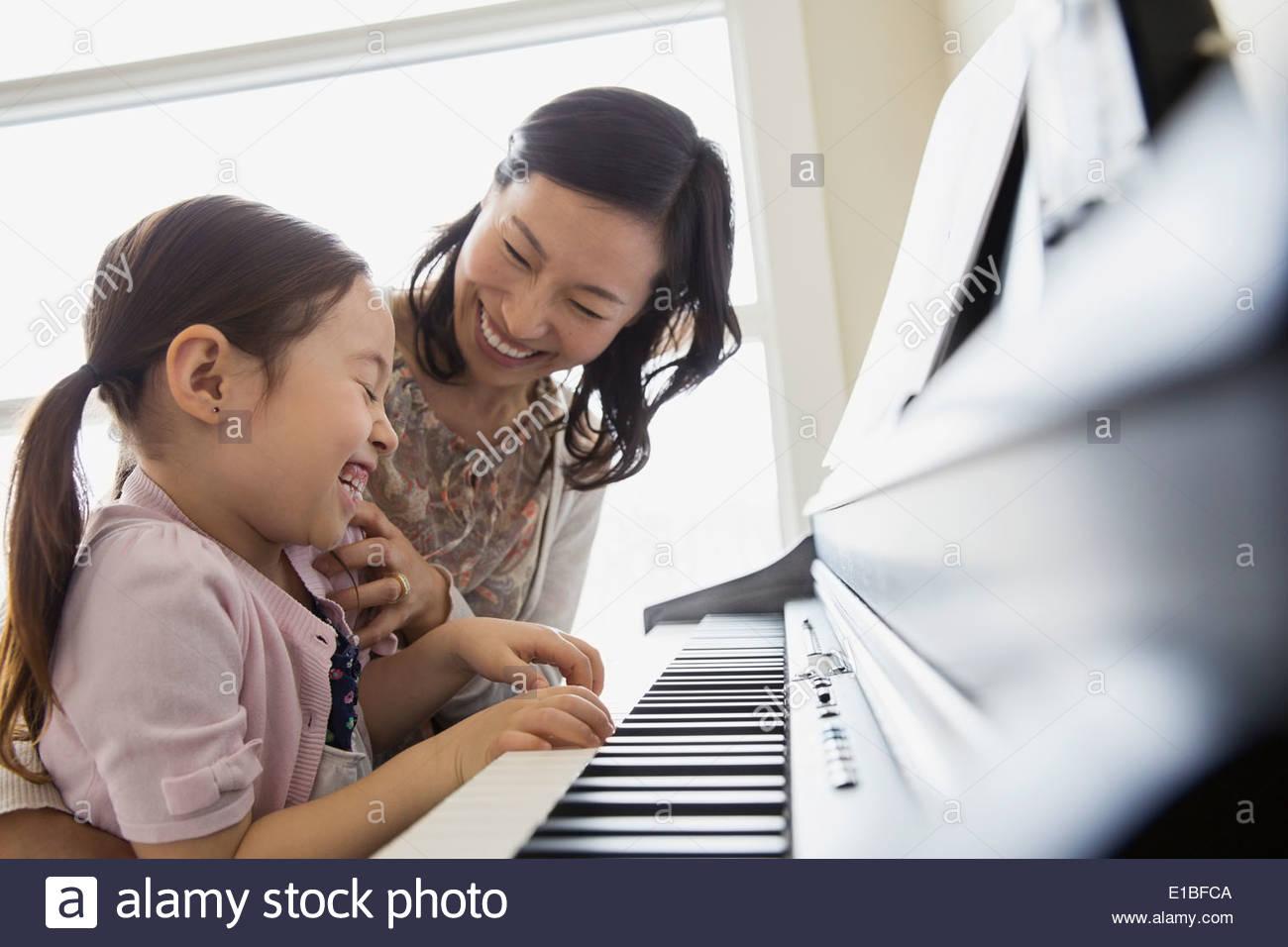 Madre Hija enseñando a tocar el piano Foto de stock