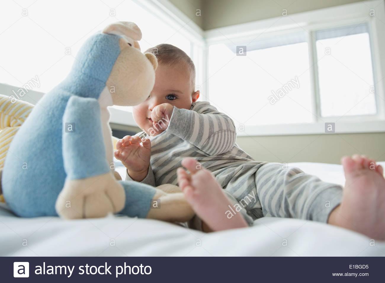 Bebé con peluche en la cama Imagen De Stock