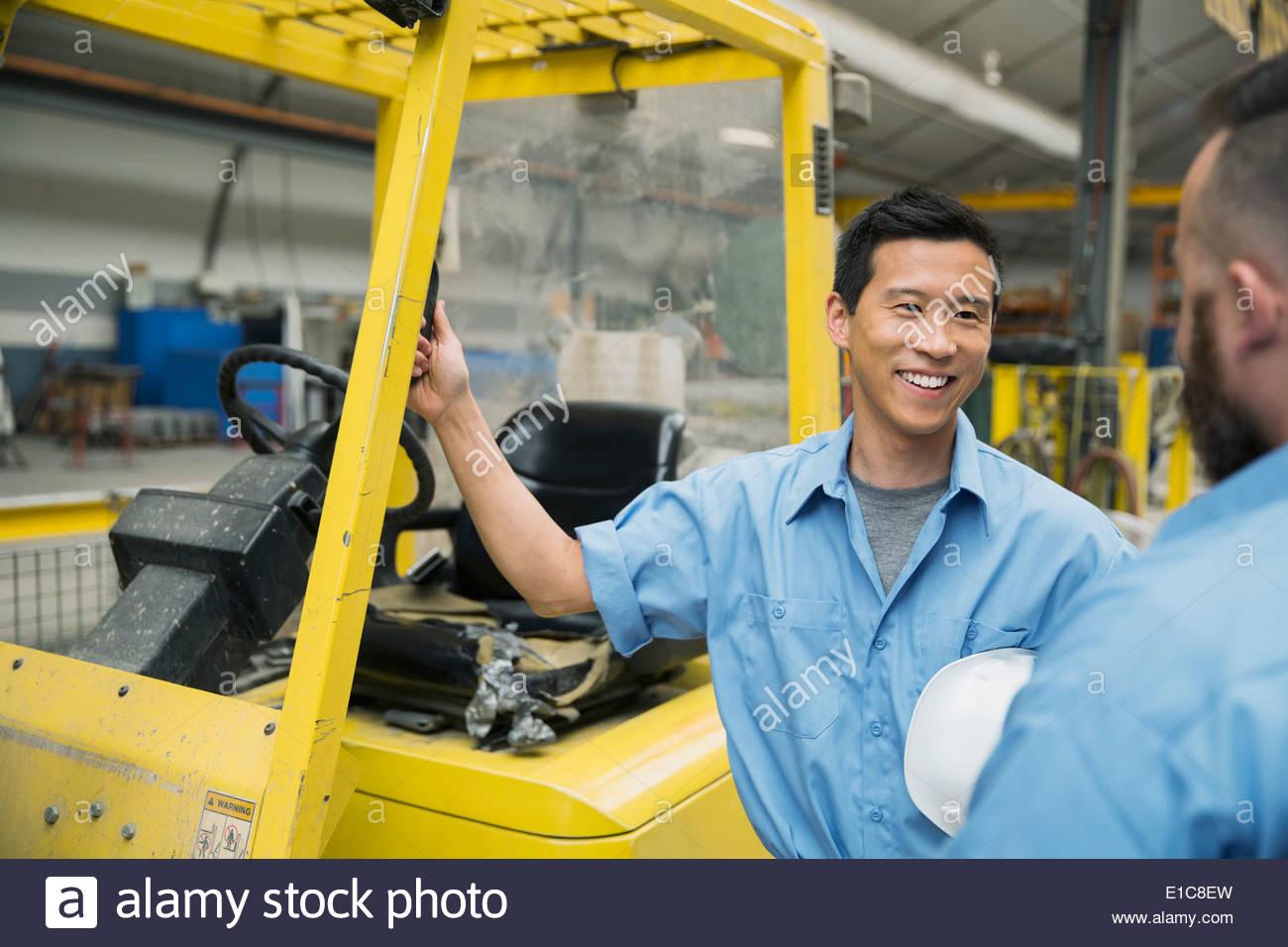 Los trabajadores hablando a la carretilla elevadora en la fábrica. Imagen De Stock