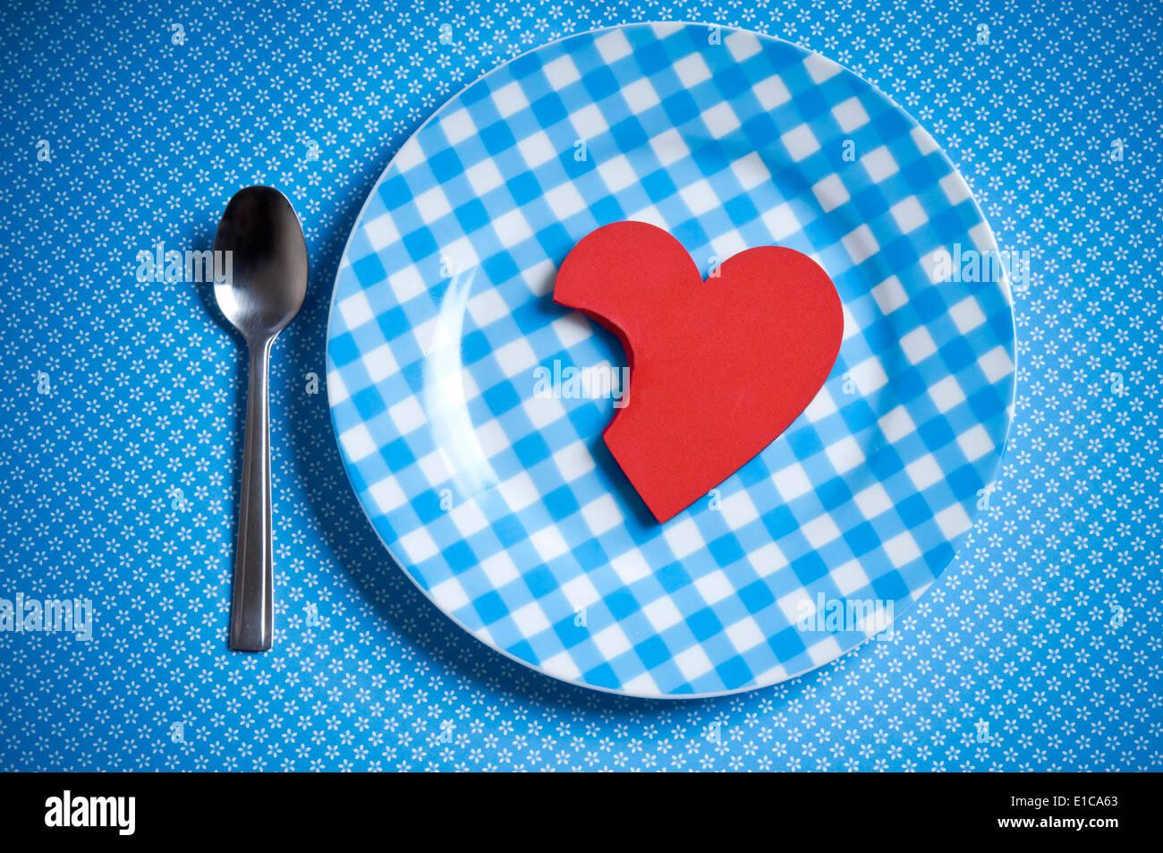 Valentine heart shape parcialmente comido en un plato, hambrientos de amor concepto Imagen De Stock