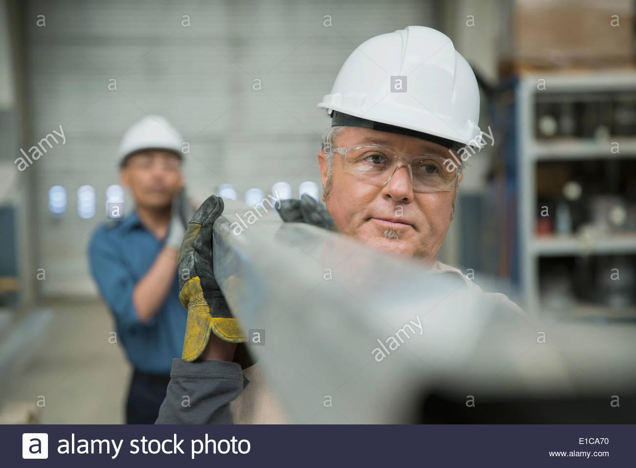 Los trabajadores que llevan vigas de acero en la planta de fabricación Imagen De Stock