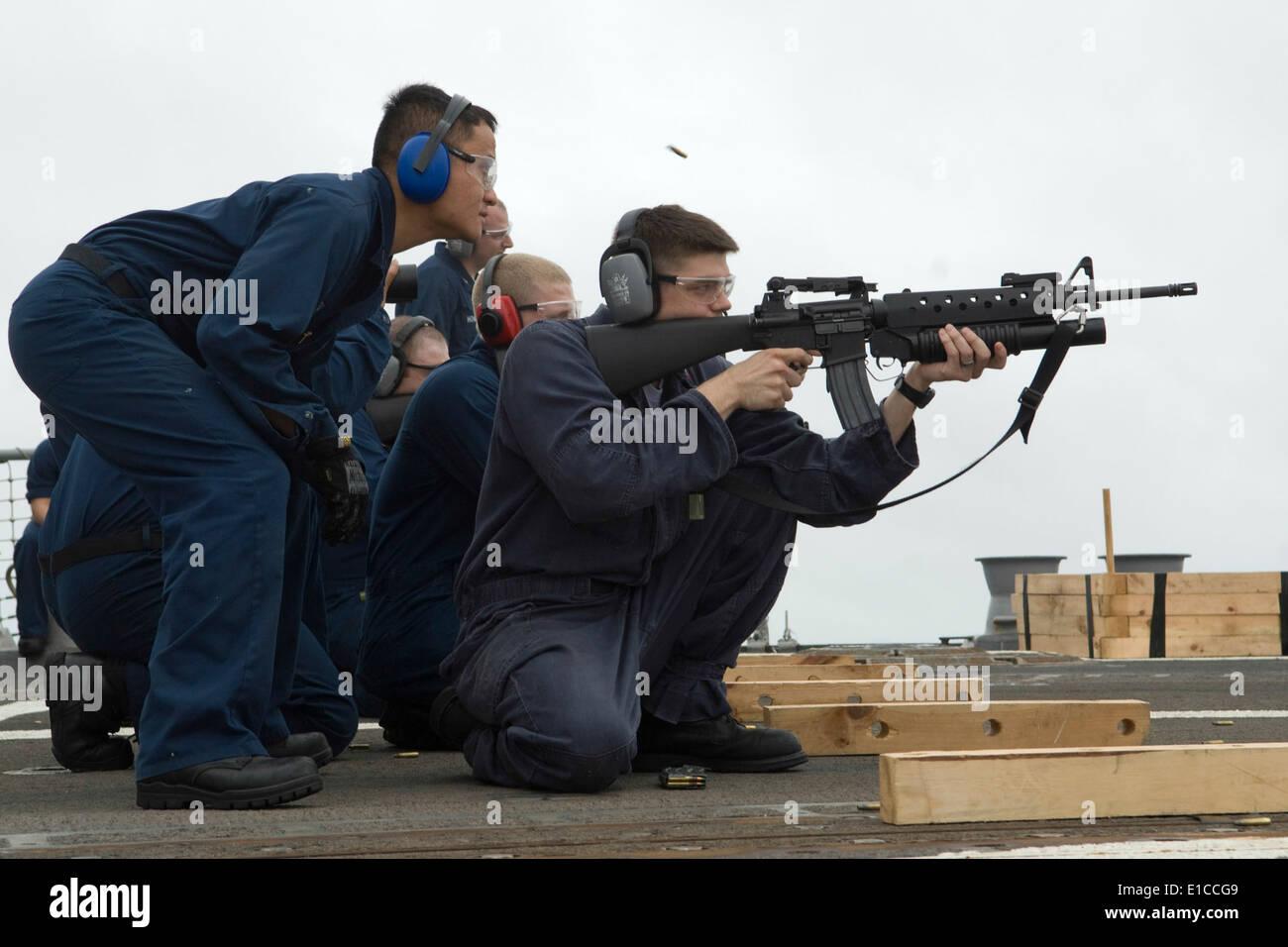 Marina de los EE.UU. 2ª clase Controlman fuego Chaung Pha observa como técnico de casco de segunda clase Briscoe Donipaul desencadena un fusil M-16 d Foto de stock