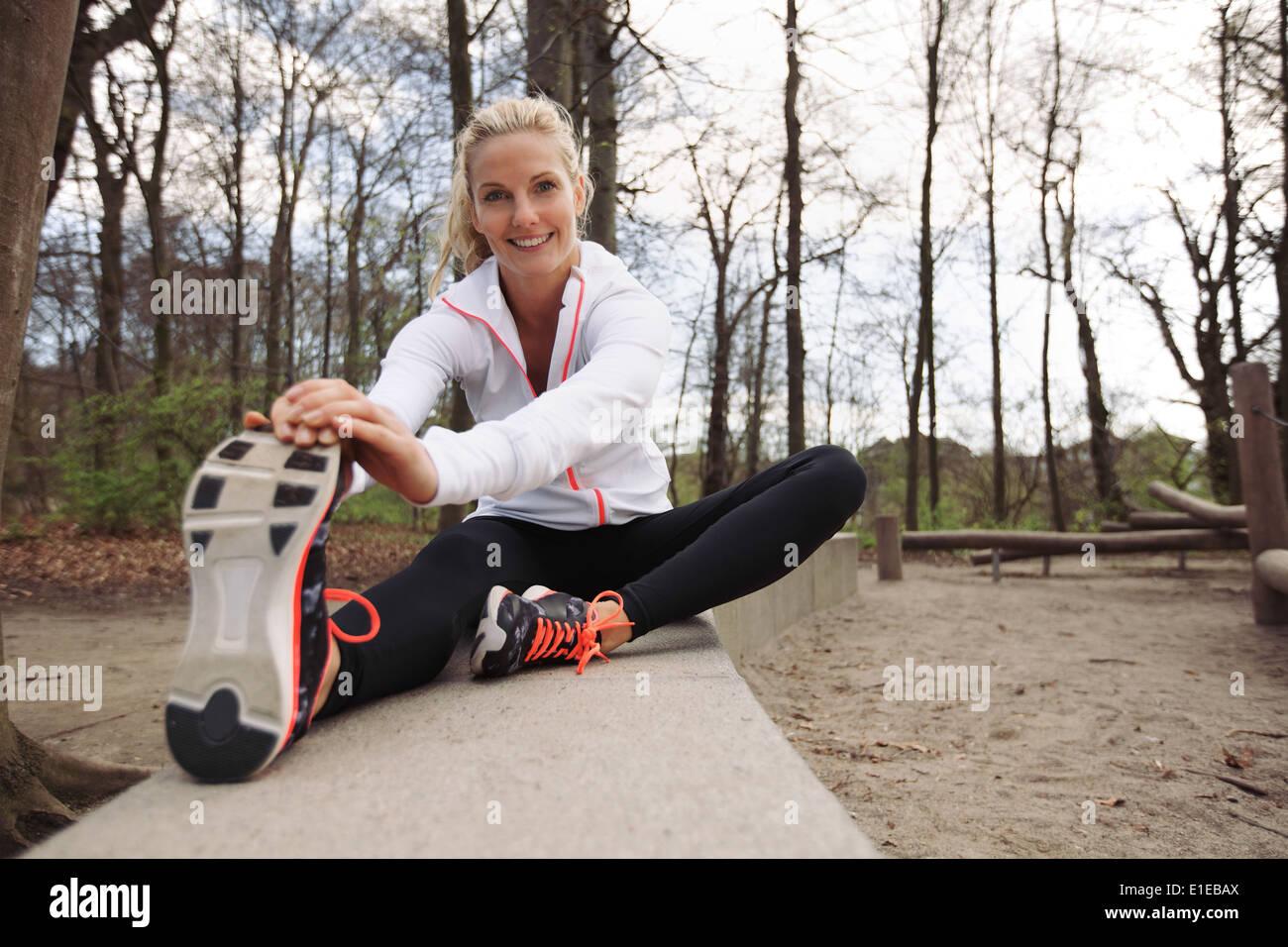 Feliz y colocar la mujer estirando sus piernas antes de la sesión de entrenamiento en la naturaleza. Hermosa atleta caucásica ejerciendo en el parque. Imagen De Stock