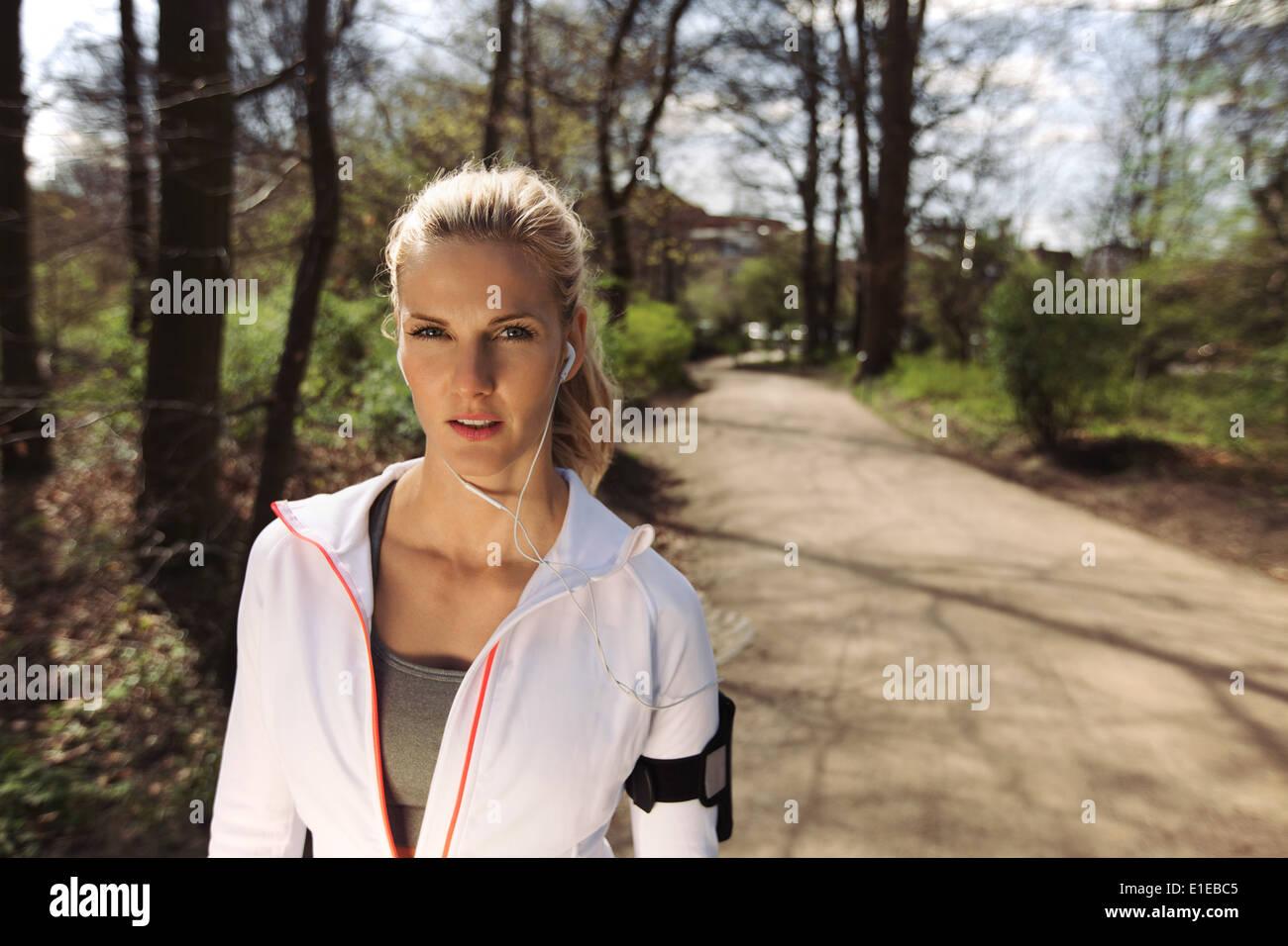 Retrato de muy joven en ropa deportiva llevar auriculares mientras en la rutina de ejercicios en el bosque. Los jóvenes corredoras Imagen De Stock