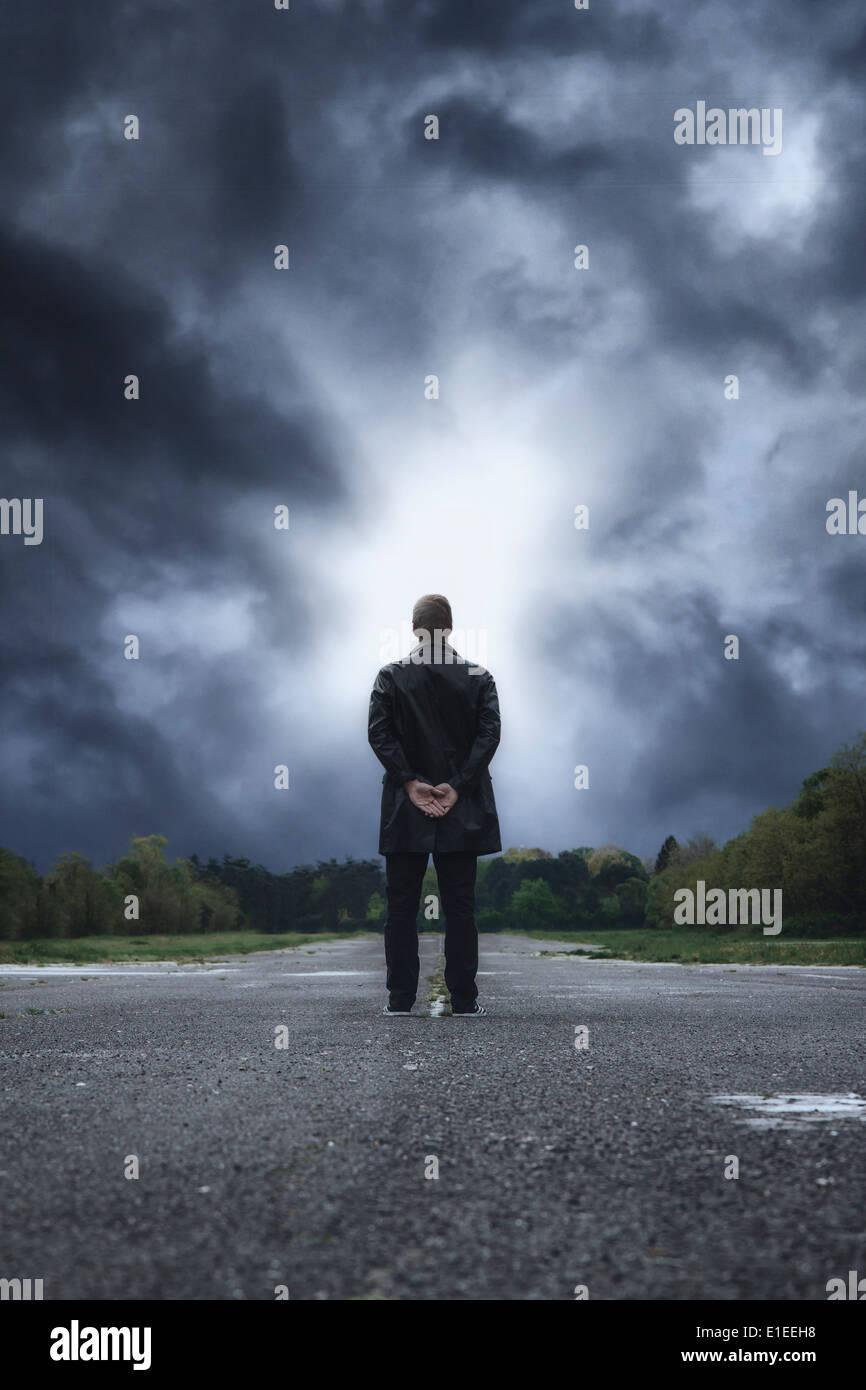 Un hombre en ropa oscura en una calle abandonada Imagen De Stock