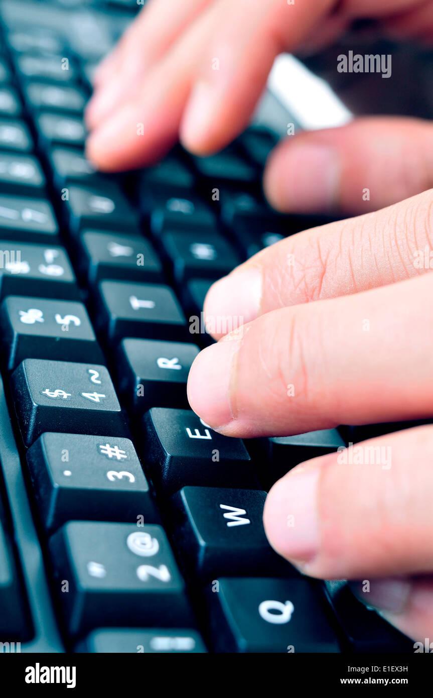 Primer plano de la mano de un hombre escribiendo en el teclado del ordenador Foto de stock