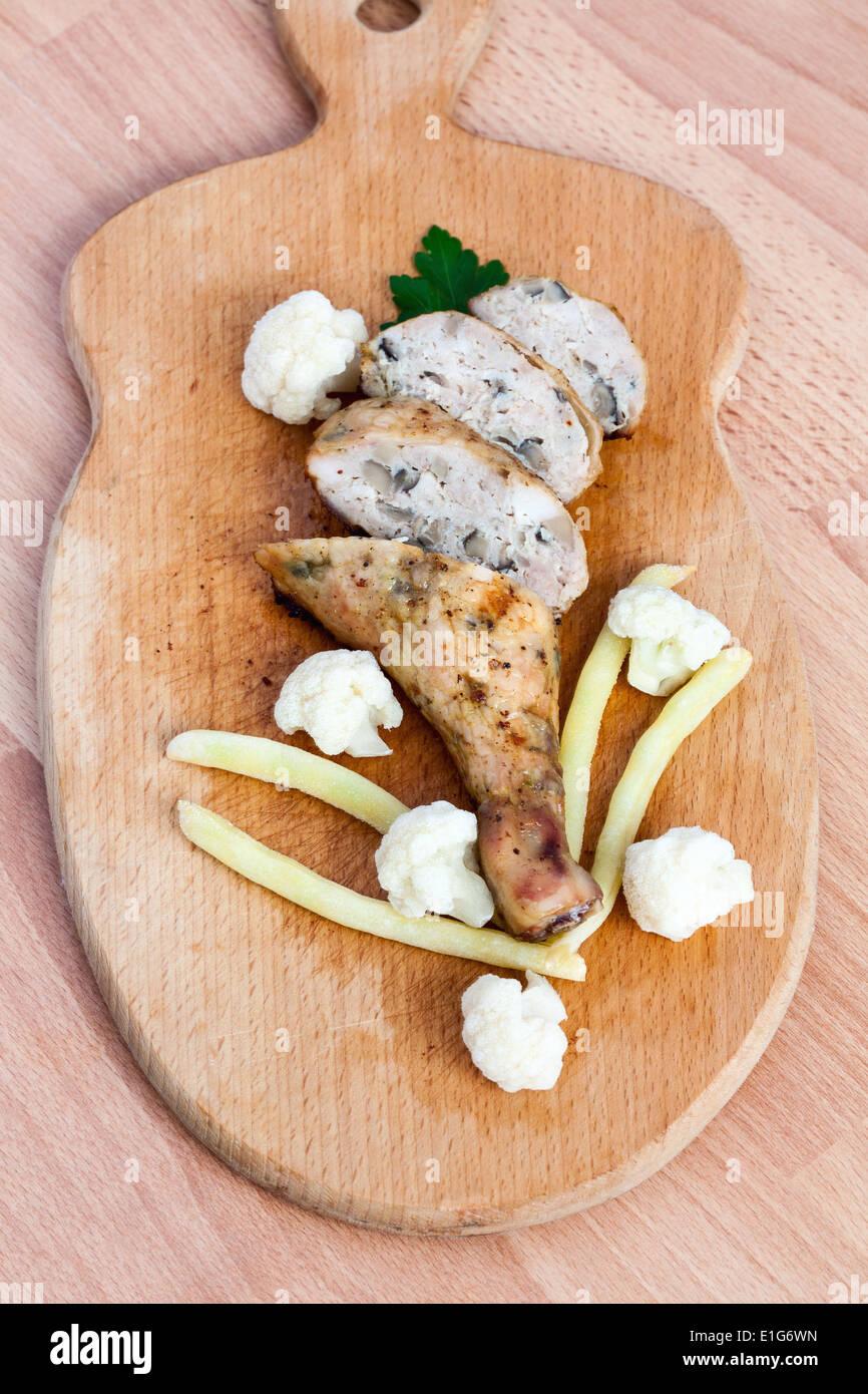 Cuartos de pollo asado a la parrilla sobre una tabla para cortar ...