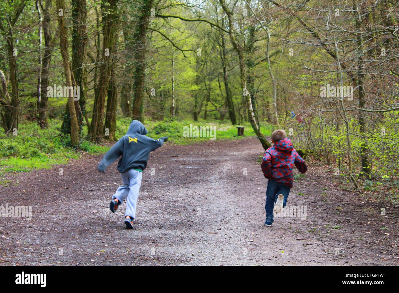 Los niños salir corriendo en una pista forestal Imagen De Stock