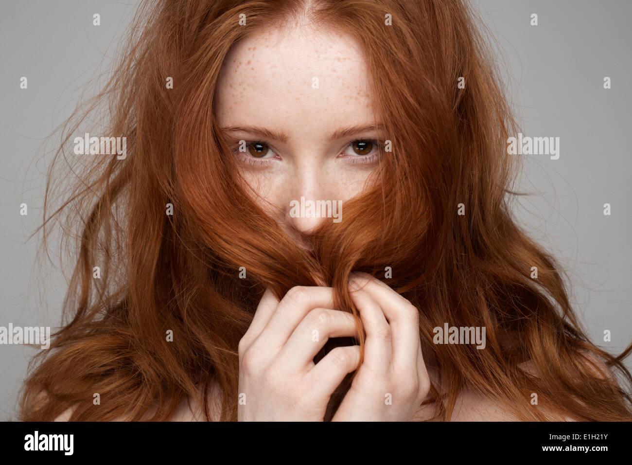 Retrato de mujer joven, las manos en el cabello Foto de stock