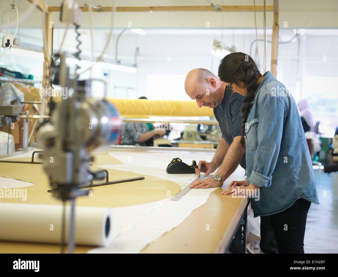 Los trabajadores de la industria de la confección capacitación en fábrica de ropa Imagen De Stock