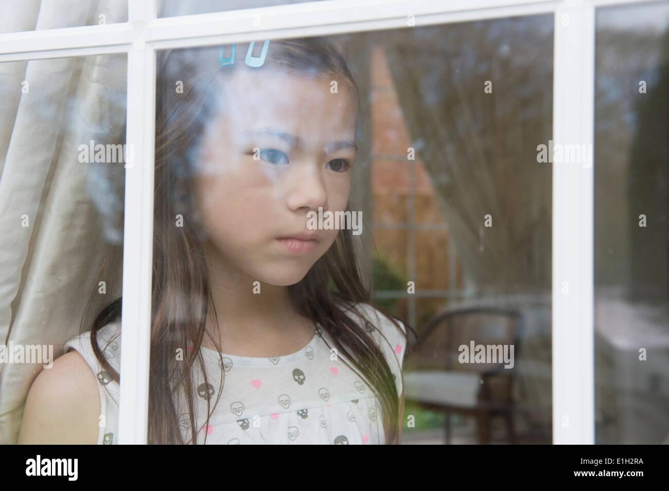 Infeliz muchacha sentada mirando desde la ventana de la habitación Imagen De Stock