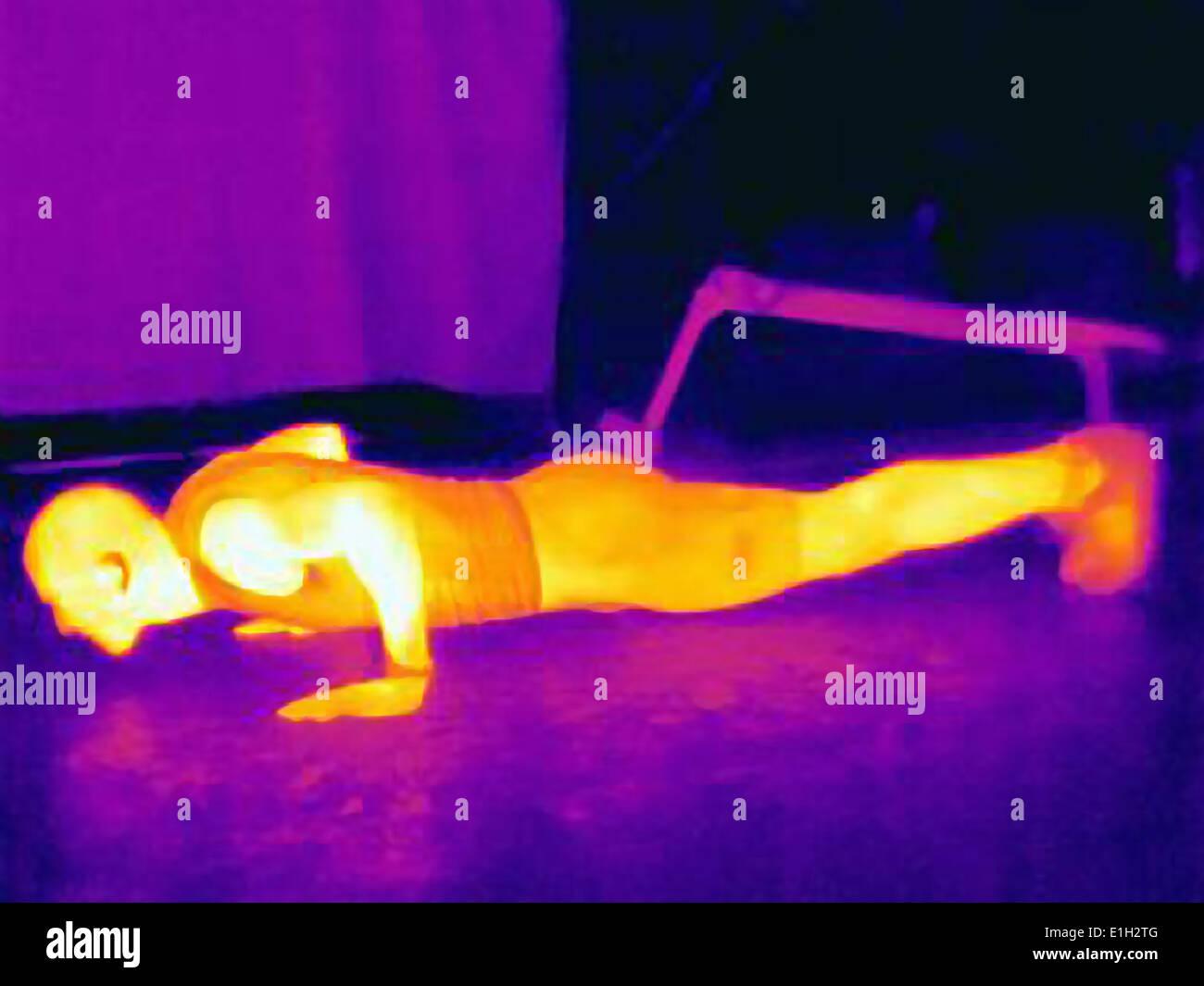 Imagen térmica del joven atleta masculino haciendo flexiones. La imagen muestra el calor producido por los músculos Imagen De Stock