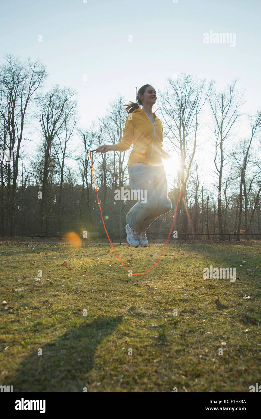 Mujer joven ejercitándose en campo con cuerdas de saltar Imagen De Stock