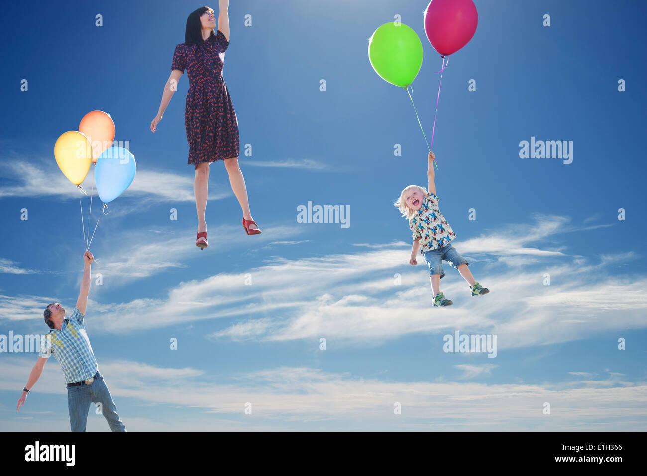 Pareja madura y joven hijo flotando hacia el cielo sujetando globos Imagen De Stock