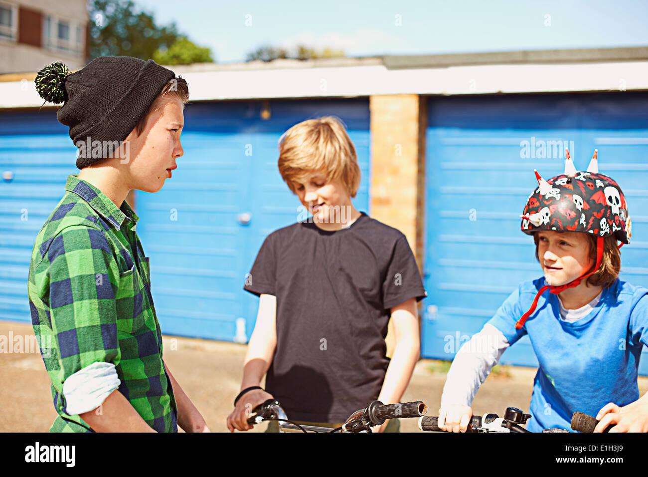 Tres muchachos hablando cerca de garajes Imagen De Stock