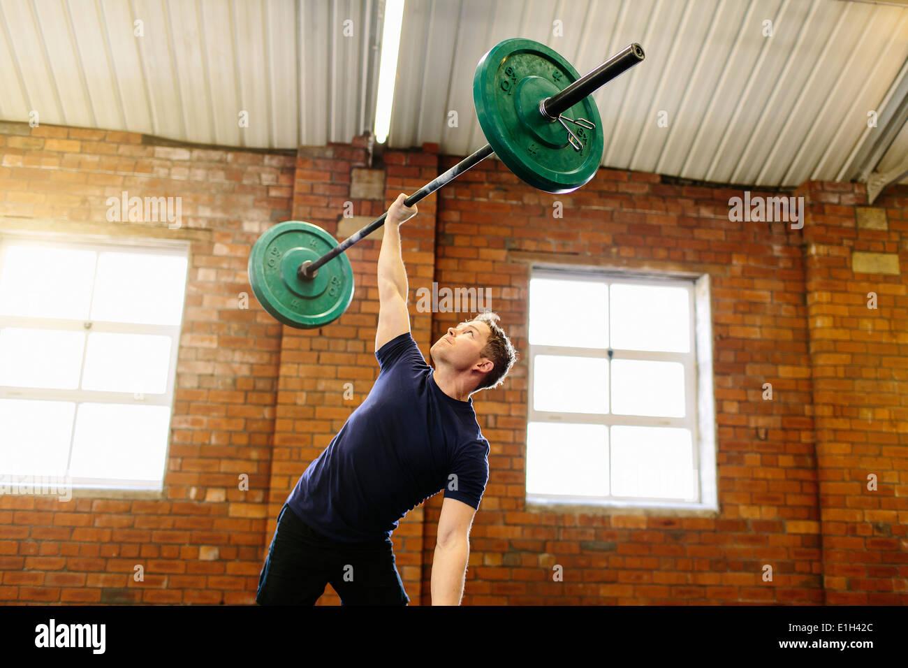 El hombre levantando barbell con una mano Imagen De Stock