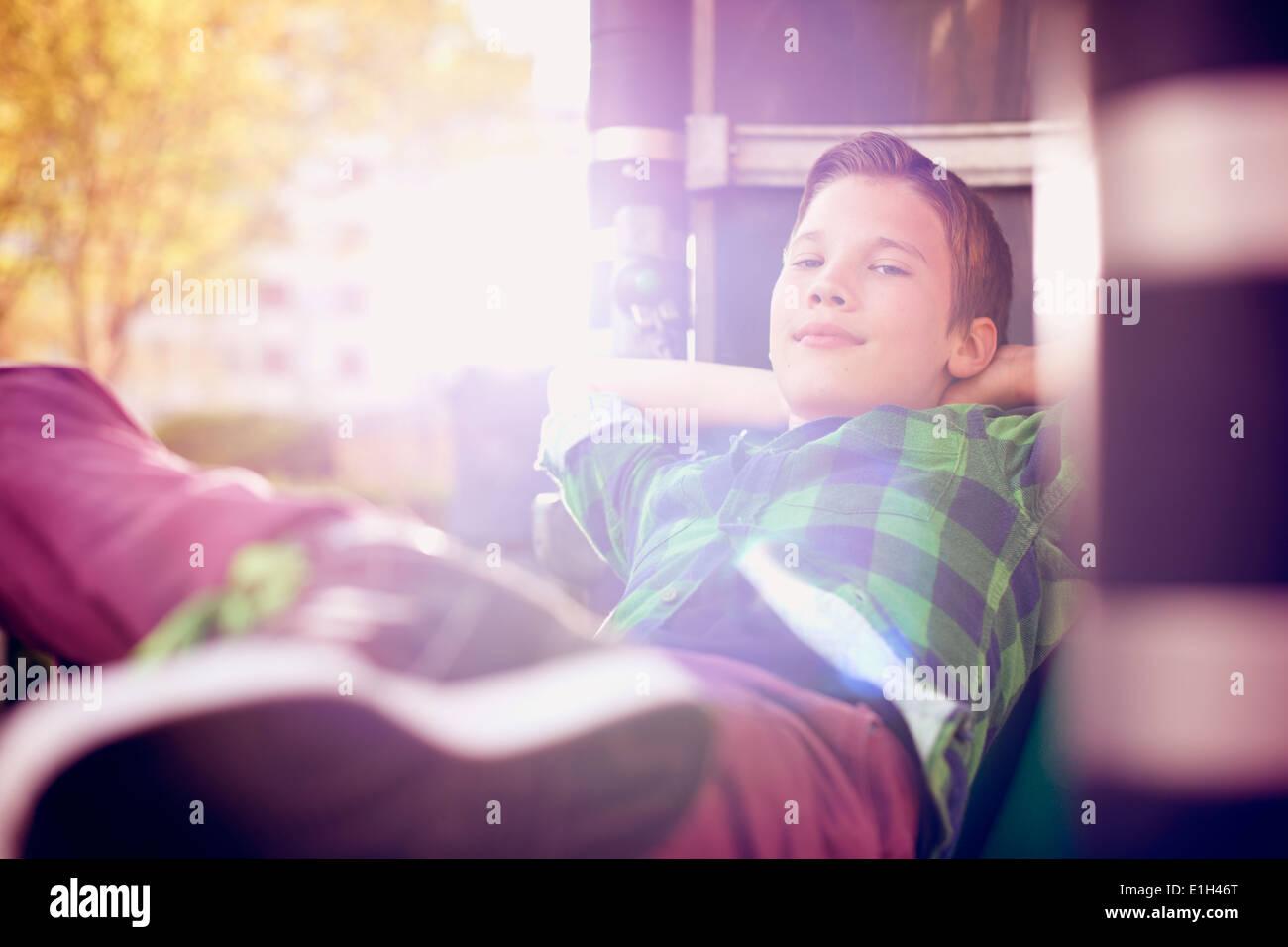 Retrato de niño relajado, con las manos detrás de la cabeza Imagen De Stock