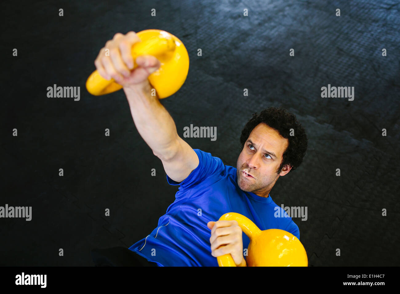 Hombre de atras levantar kettlebells Imagen De Stock