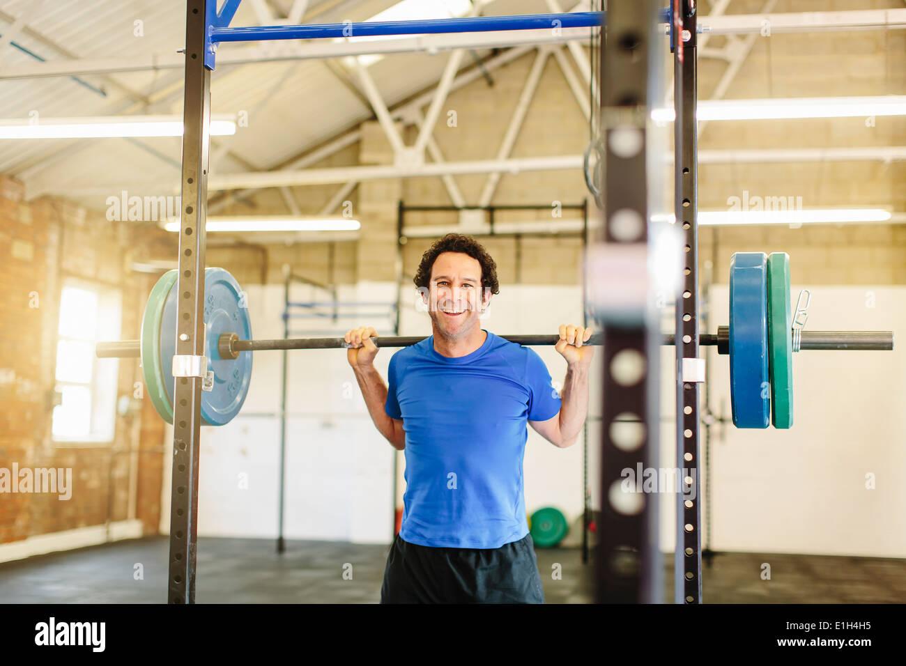 El hombre levantando barbell en gimnasio Imagen De Stock
