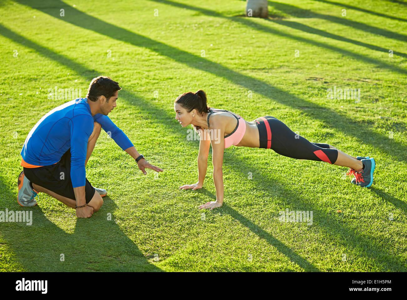 Entrenador personal con la mujer haciendo ejercicio tablón Imagen De Stock