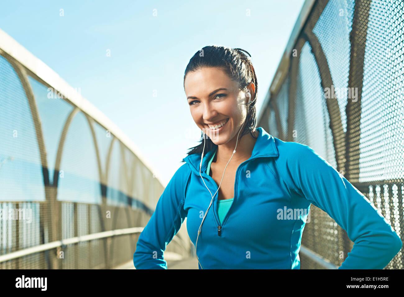 Mujer adulta media vistiendo ropa deportiva de pie en el puente Imagen De Stock