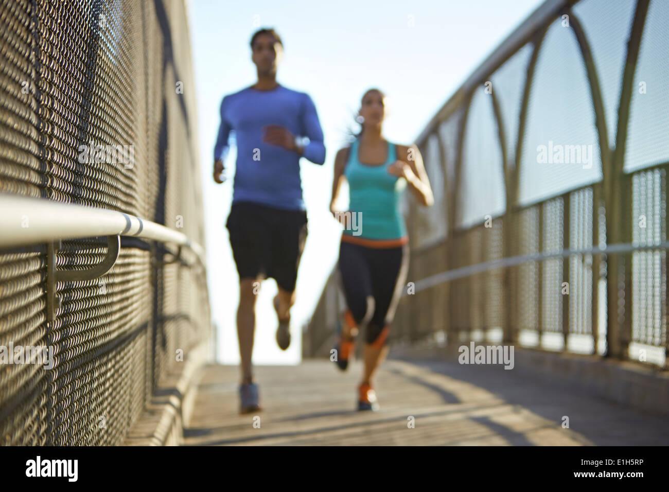Un hombre y una mujer que se ejecuta a través de puente Foto de stock