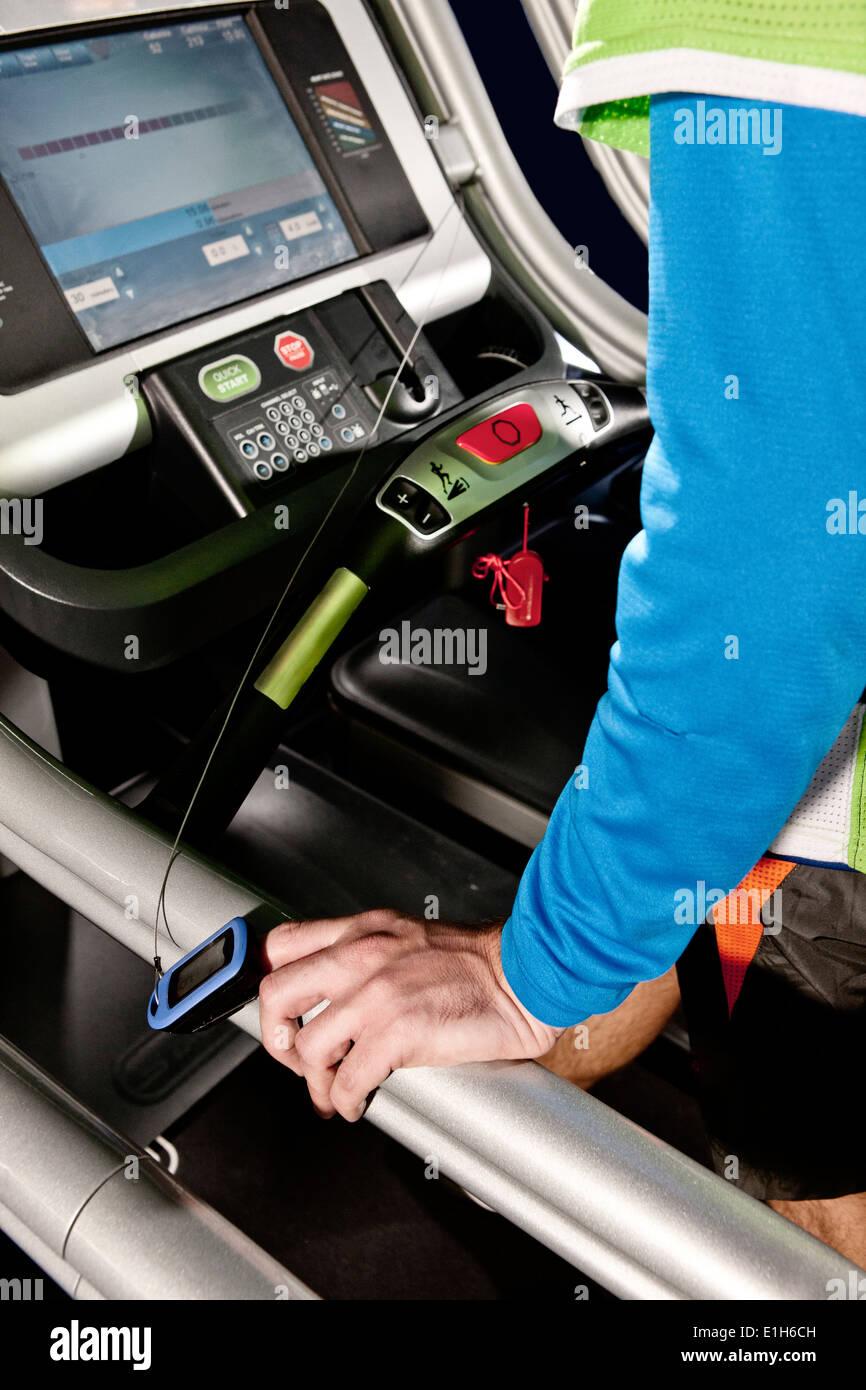 Cerca del brazo macho y monitor de ritmo cardíaco en la caminadora del gimnasio en el centro de altura Imagen De Stock