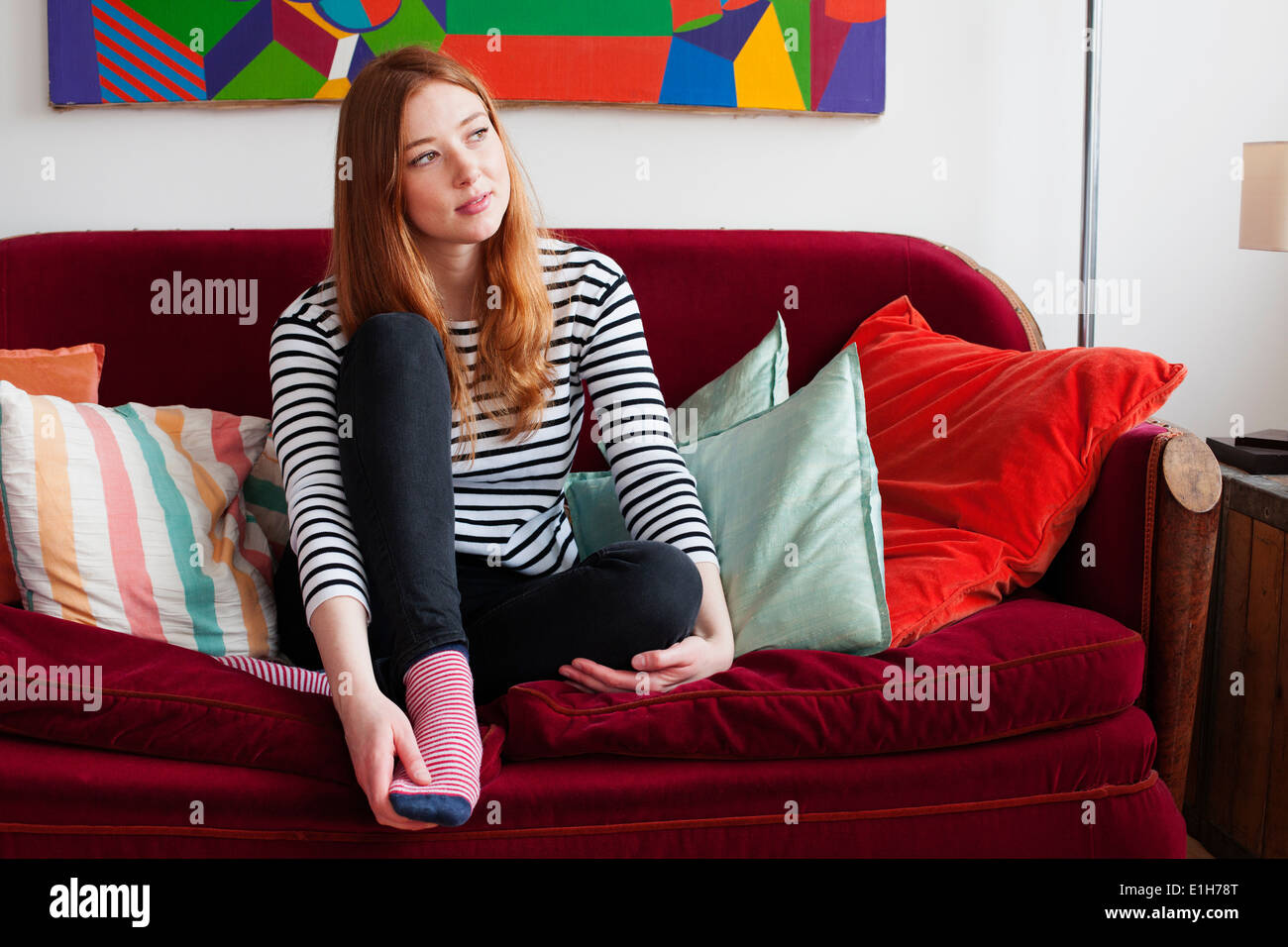 Mujer joven sentada en un sofá con patas arriba Imagen De Stock
