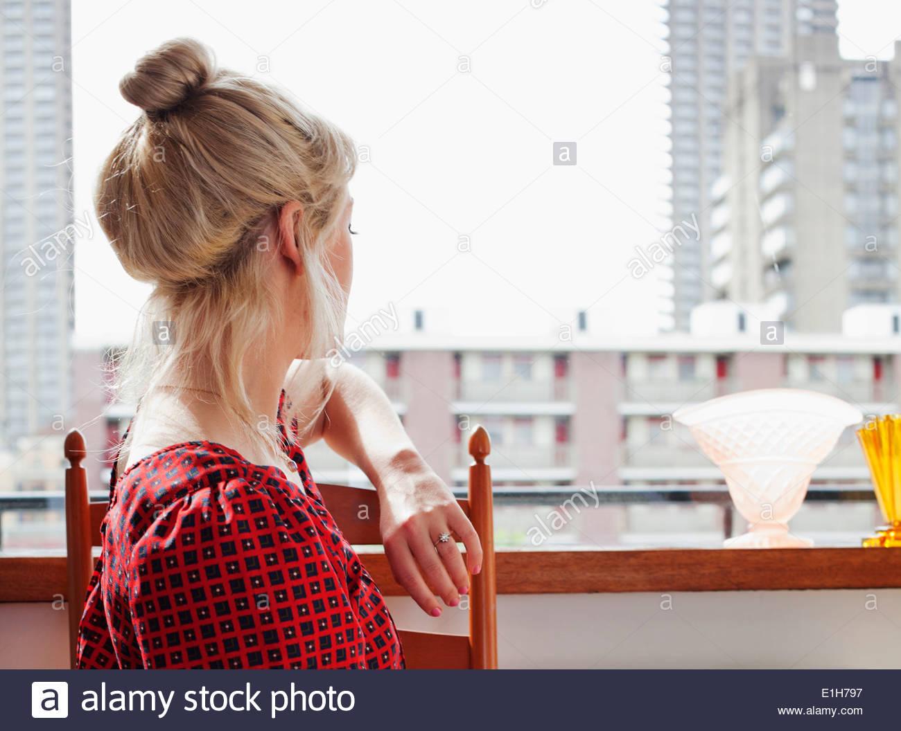 Mujer joven mirando hacia afuera de la ventana Imagen De Stock