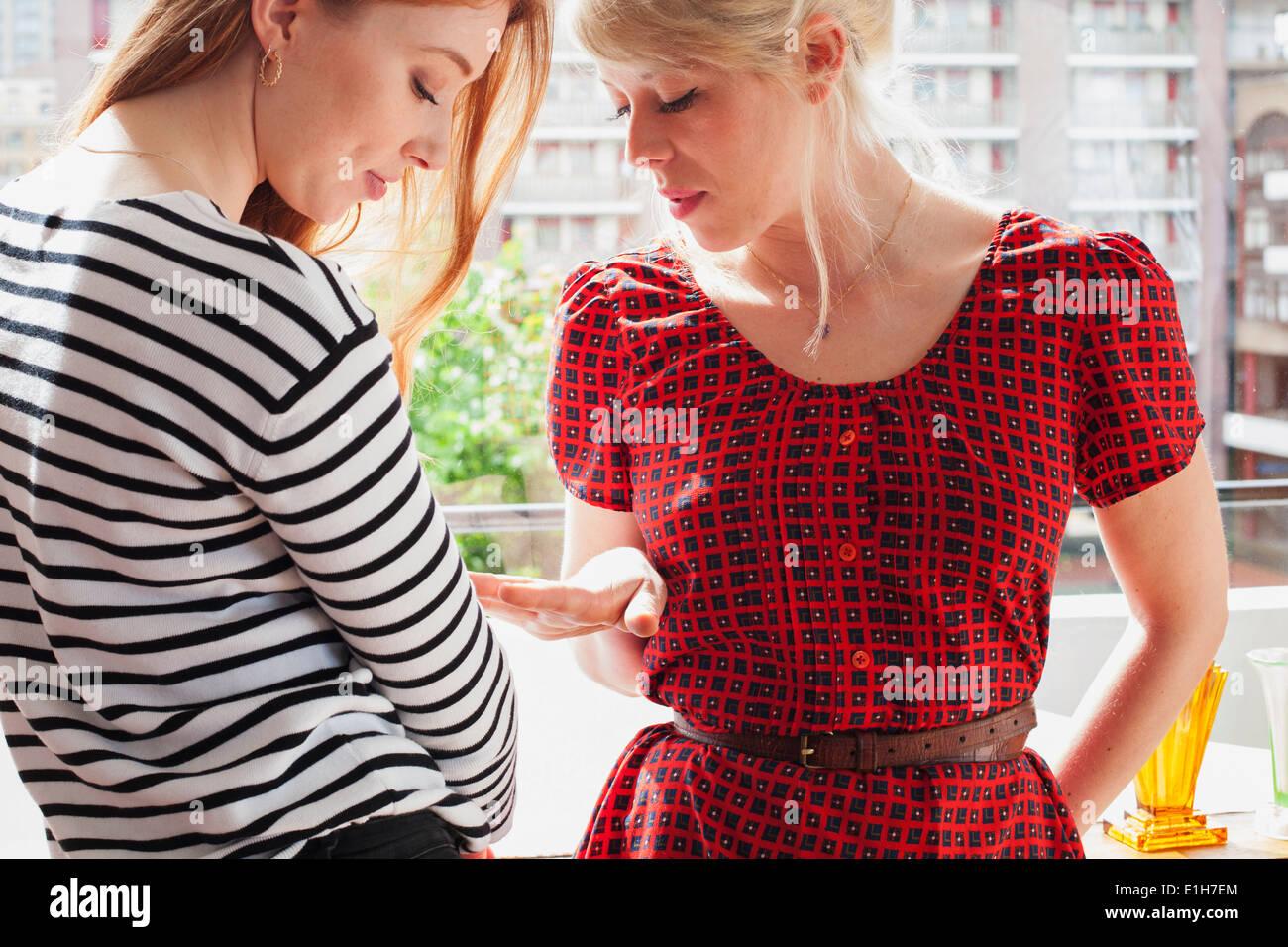 Las mujeres jóvenes mirando las uñas Imagen De Stock