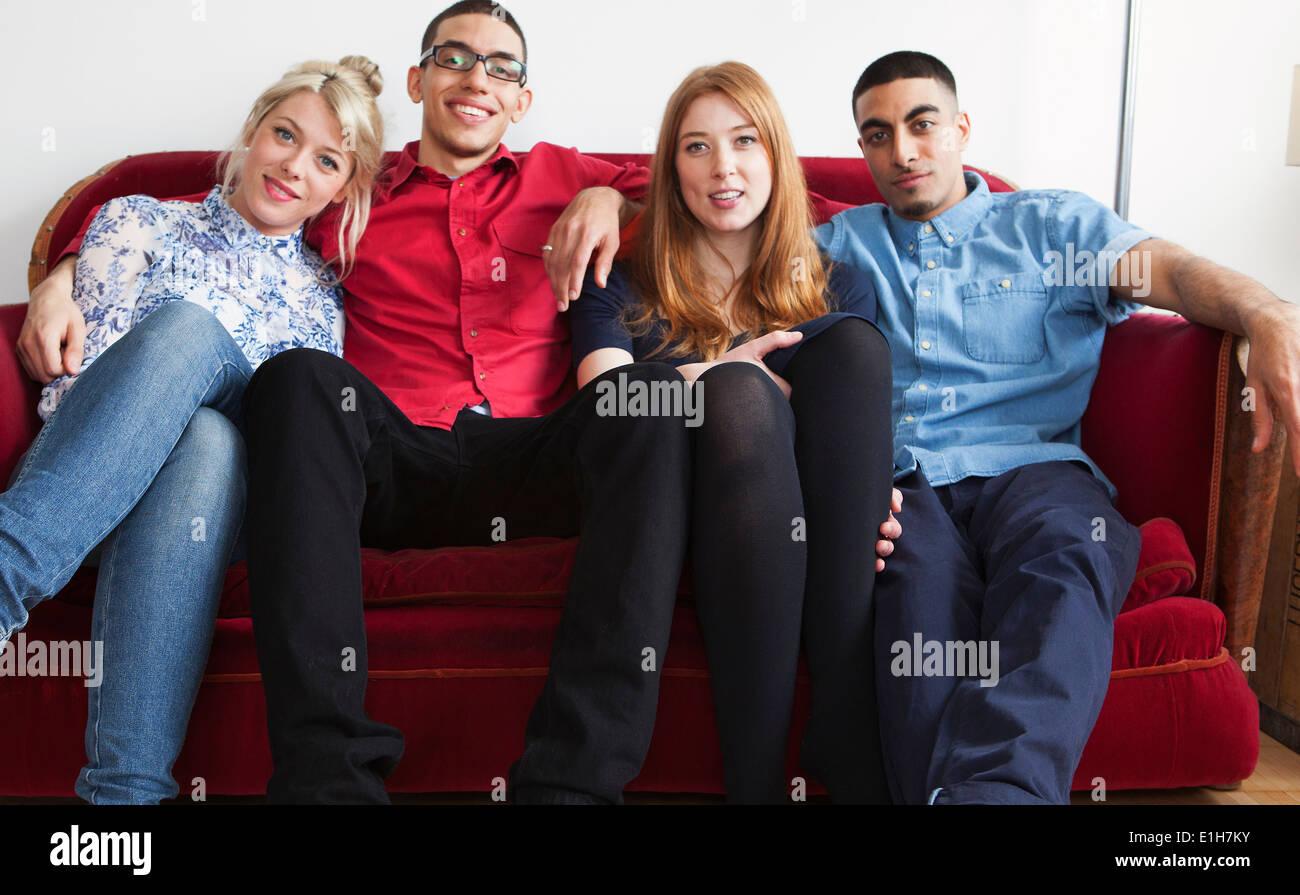 Cuatro adultos jóvenes sentados en el sofá Imagen De Stock