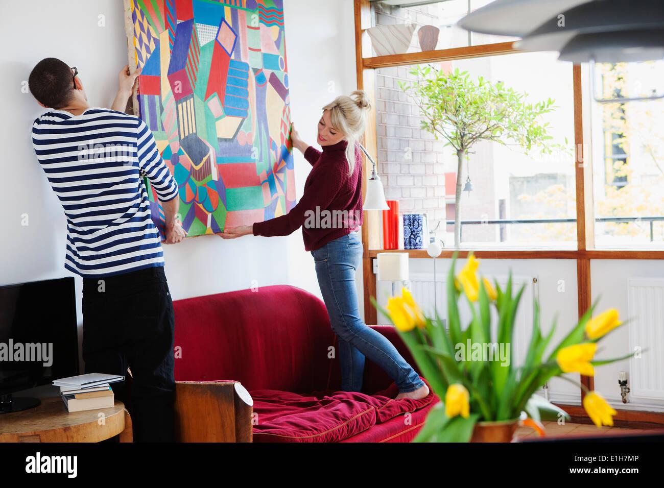 Pareja joven poniendo pintura en salón Imagen De Stock