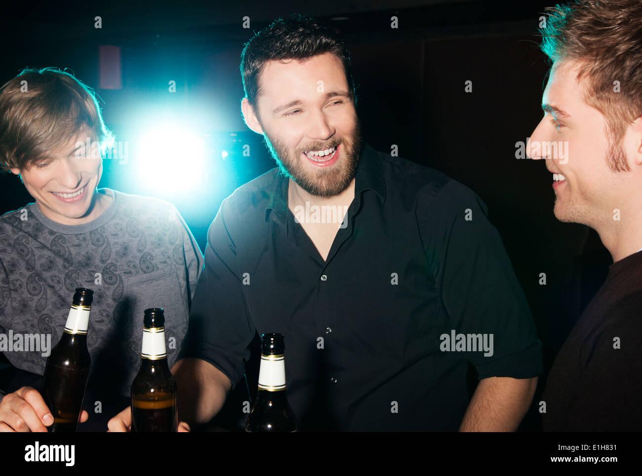 Tres amigos varones bebiendo cerveza embotellada en discoteca Foto de stock