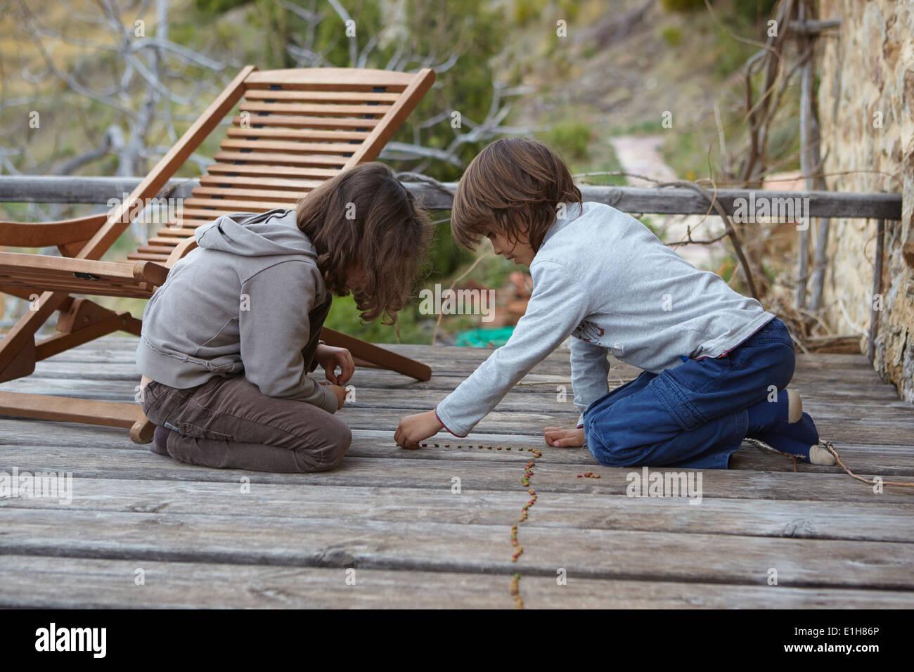 Hermano y hermana, haciendo una fila de frijoles secos en el balcón Imagen De Stock