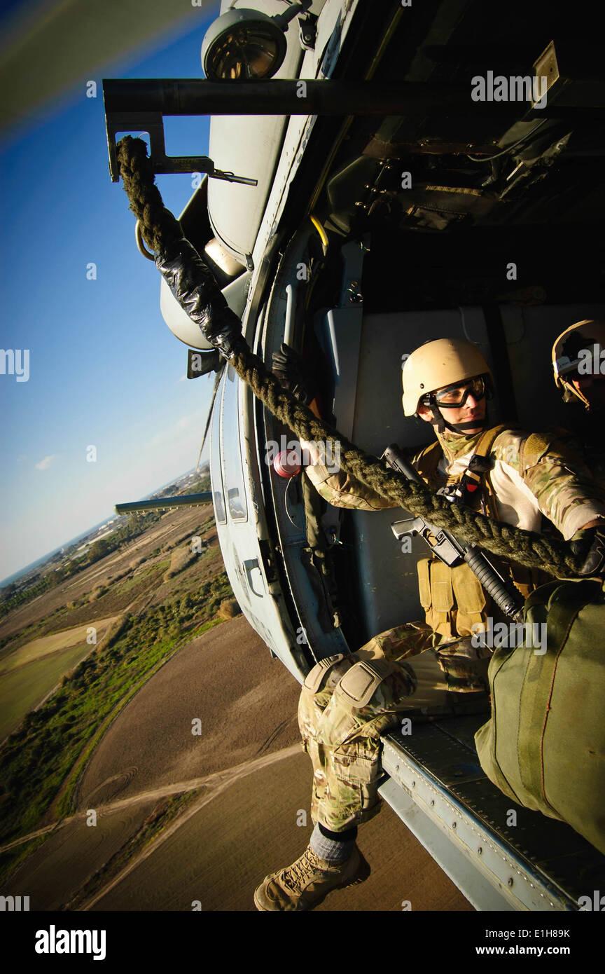 Un marinero estadounidense cabalga en un MH-60 Seahawk desde helicópteros de combate de mar Squadron (HSC) 28 durante la formación de la suspensión con Sailo cuerda Imagen De Stock