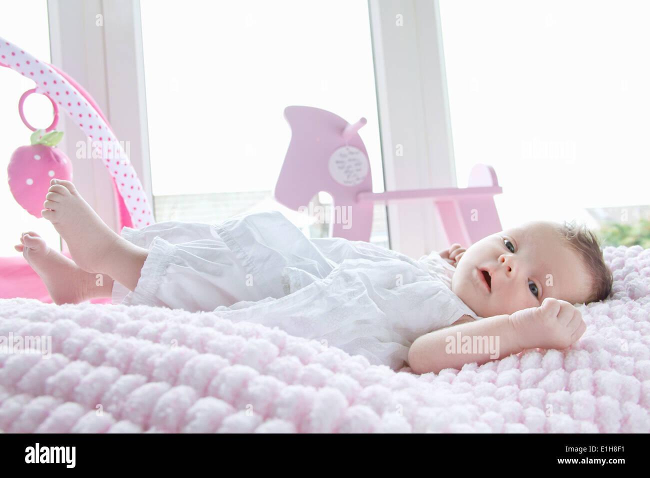 Acostado en la cama de bebé niña Imagen De Stock