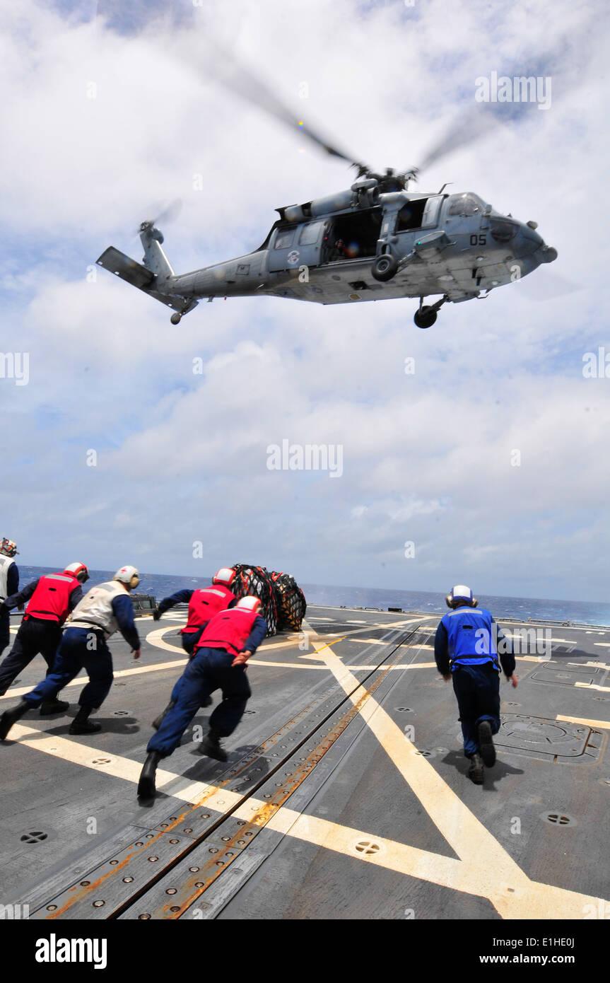 Los marineros de EE.UU. asignados al misil destructor USS McCampbell (DDG 85) ejecutar para recuperar palets de suministros entregados por un Foto de stock