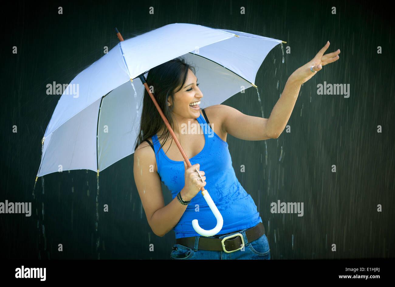 Mujer sonriente sosteniendo un paraguas, disfrutando de la lluvia Foto de stock
