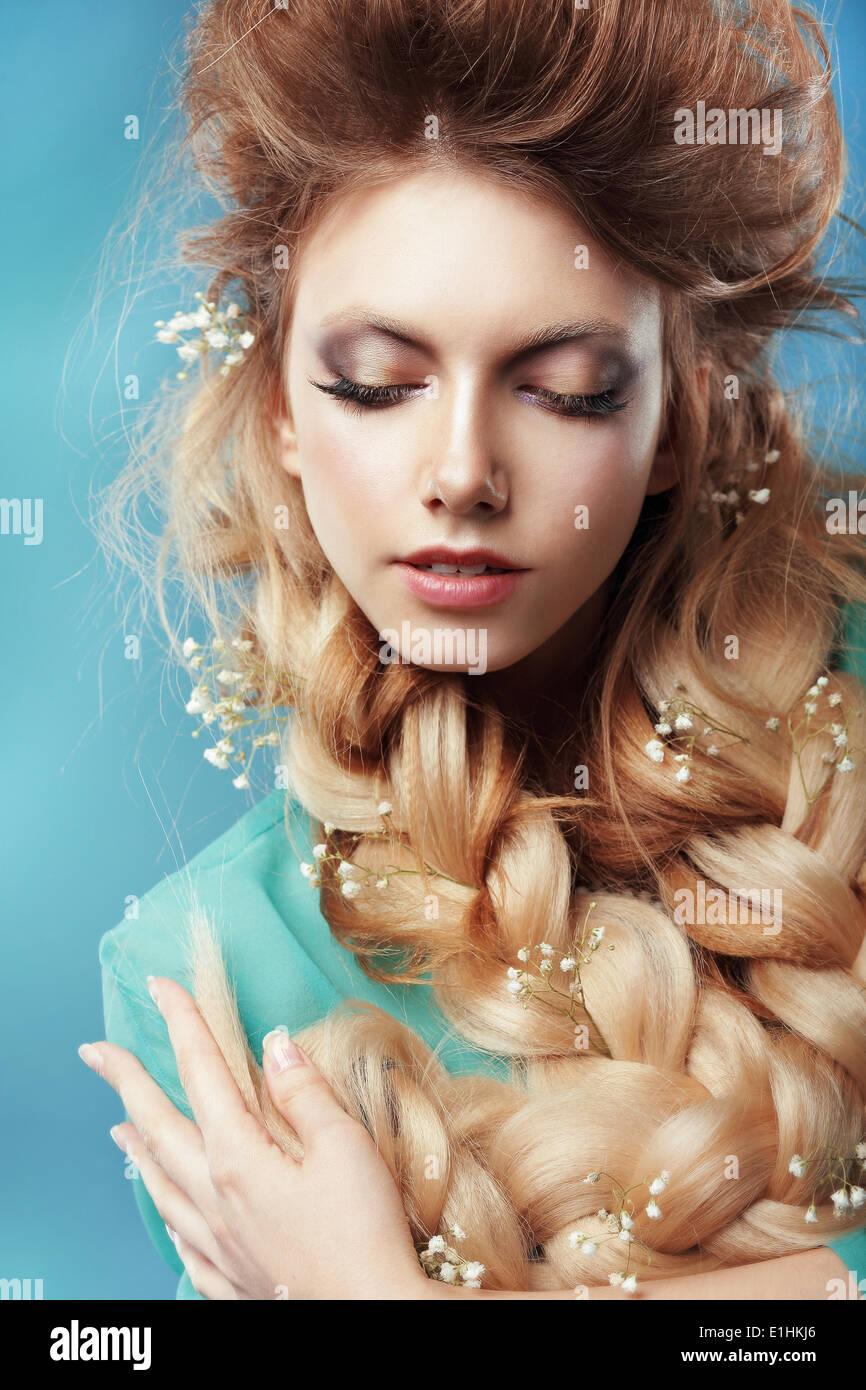 Disfrute. Mujer con trenza y flores entrelazadas Imagen De Stock