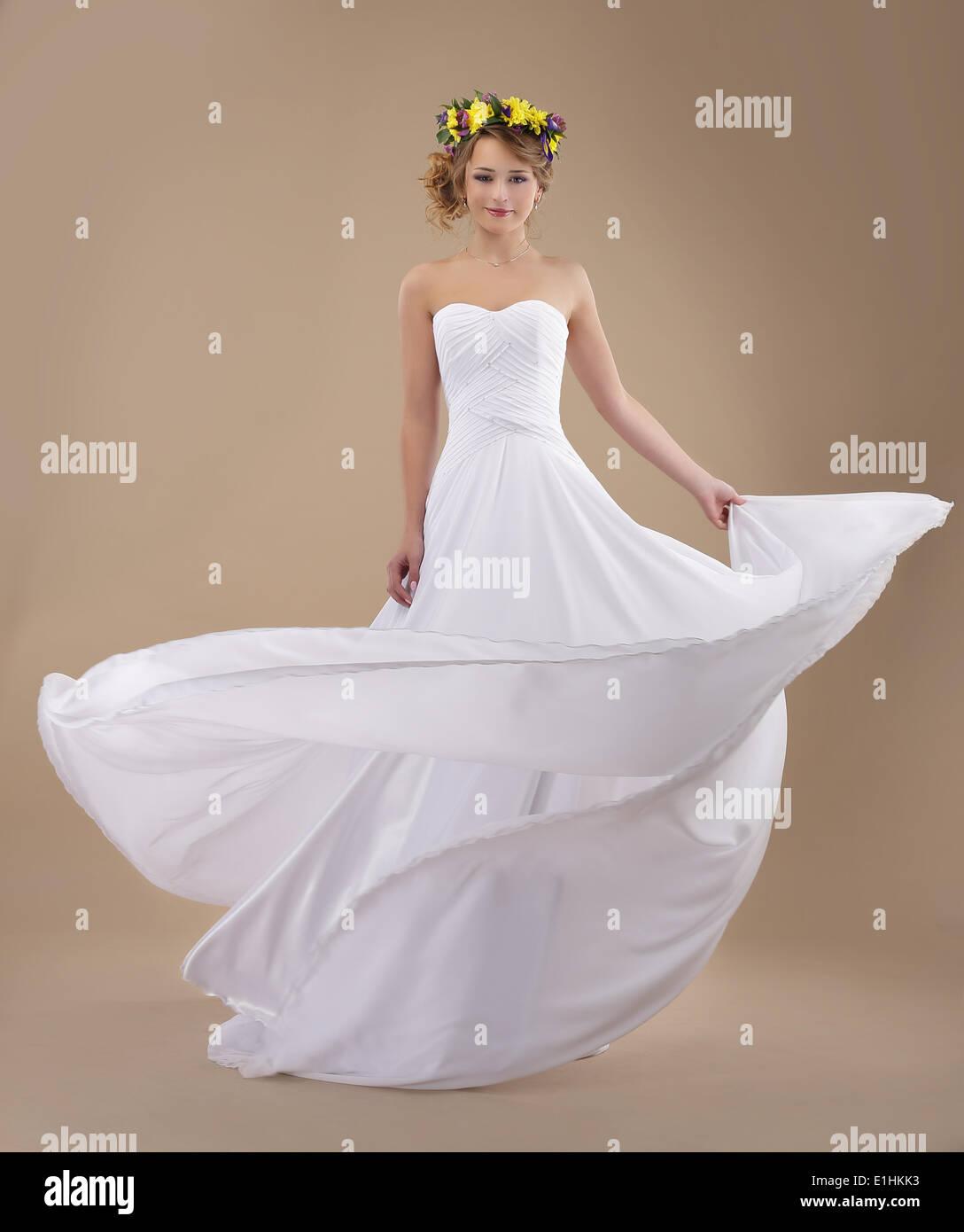 El movimiento. Mujer con corona de flores y ondeando vestido de luz Imagen De Stock