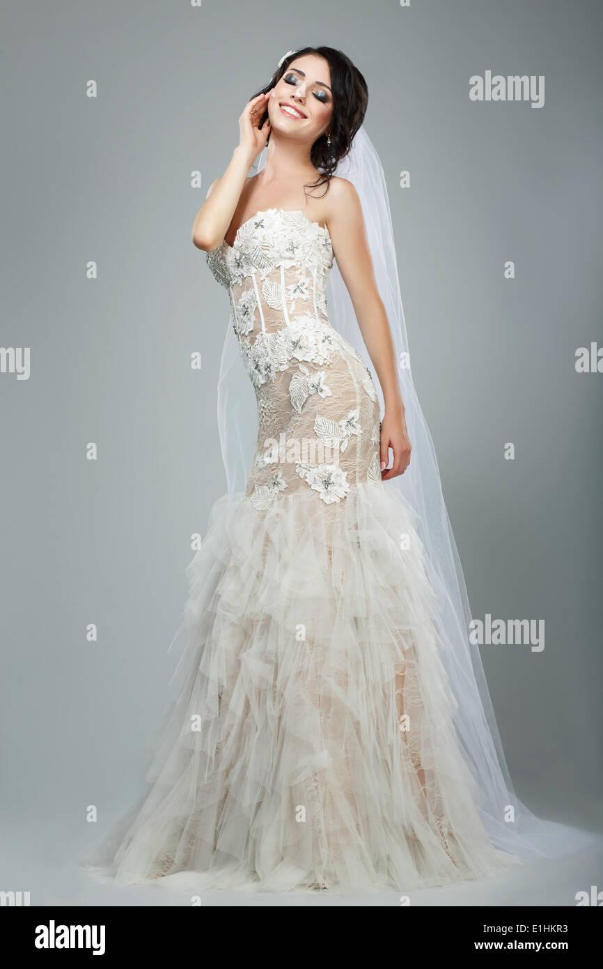 Dreaminess. La longitud completa de la novia feliz con los ojos cerrados en vestido blanco sin mangas Imagen De Stock