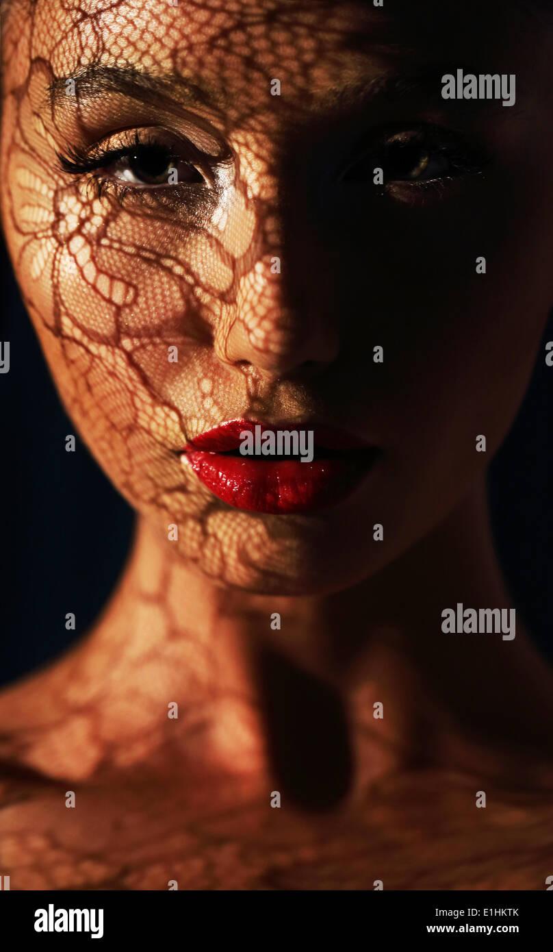 La reflexión. Mujer en sombras con reflejo de calados encaje en su cara Imagen De Stock