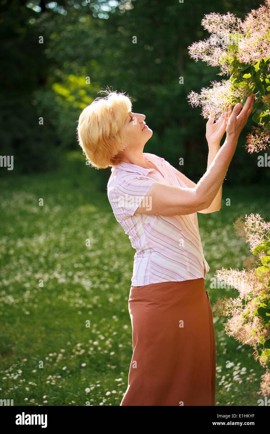 Jardinería. Elegante Mujer Senior y flores. Imagen De Stock