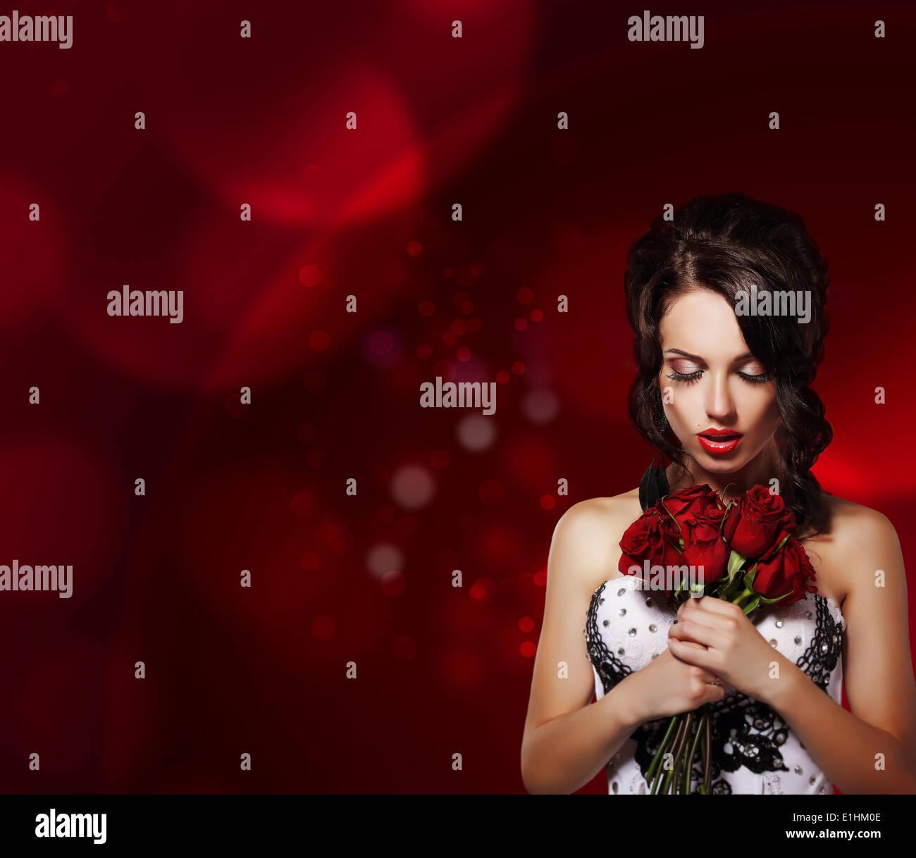 La ternura. Mujer de ensueño con bouquet de flores sobre fondo púrpura Imagen De Stock
