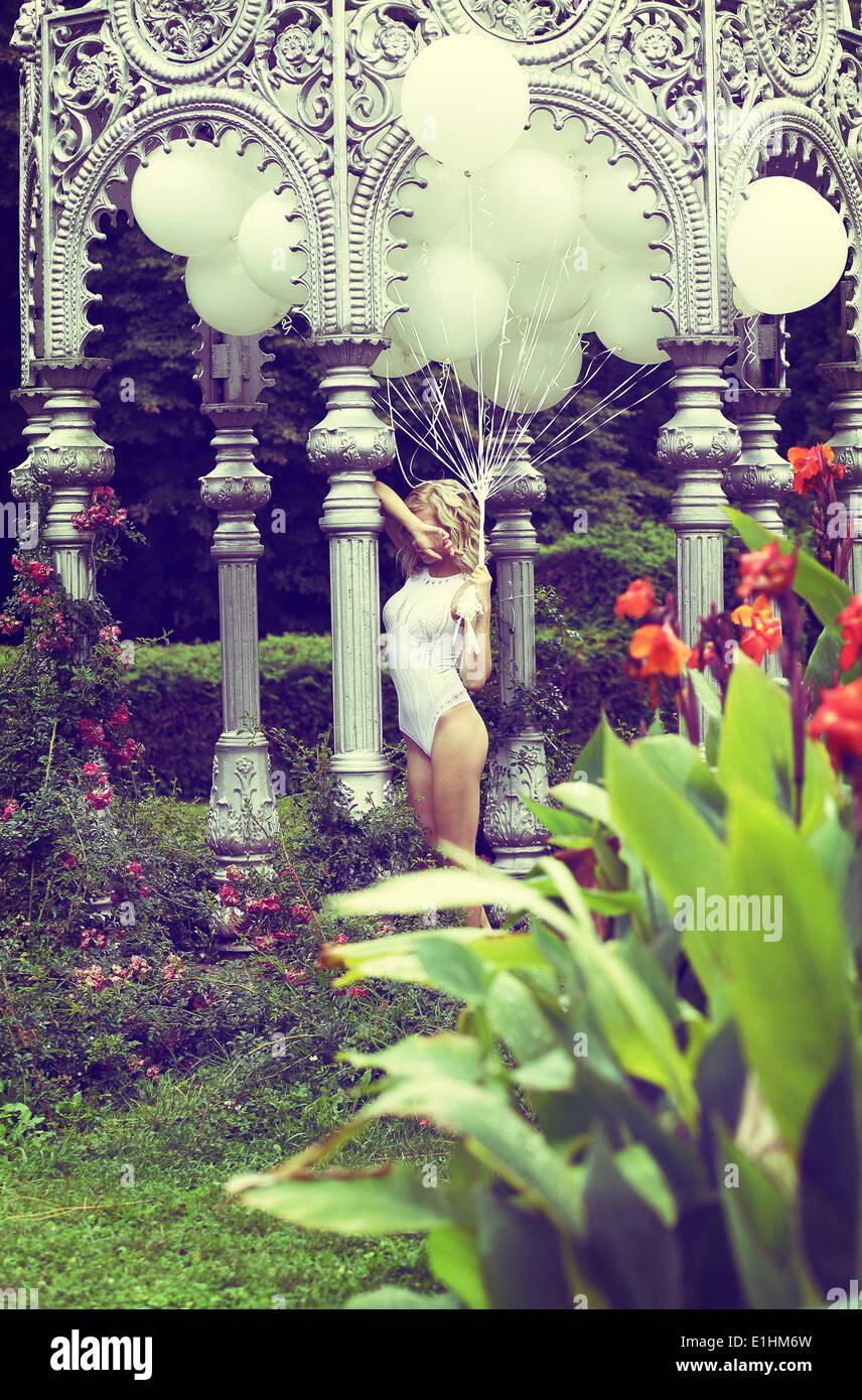 Sentimiento. Hermosa rubia relajado sosteniendo los globos de aire en el jardín Imagen De Stock