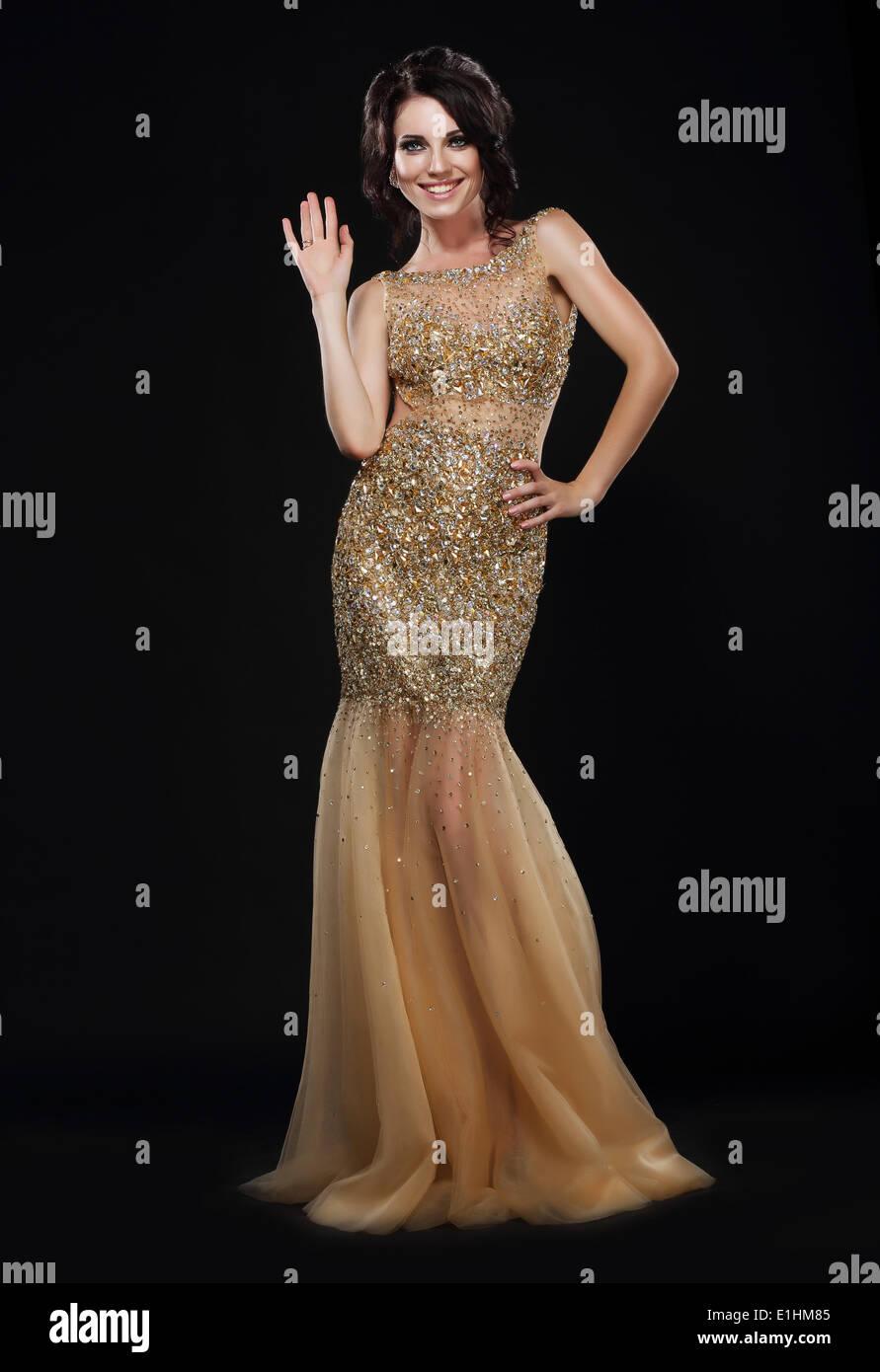El Stylishness. Mujer joven bien vestido de largo vestido dorado Imagen De Stock