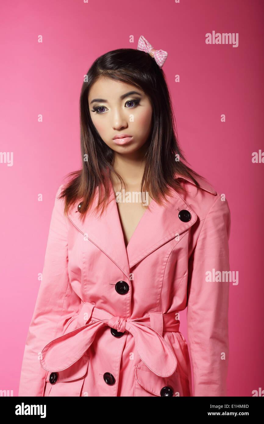 Chica japonesa elegante en color rosa Outwear sobre fondo de color Imagen De Stock